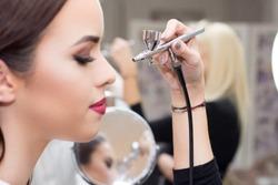 Makeup artist using airbrusher.