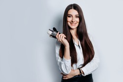 Makeup artist with brushes in hand on a white background