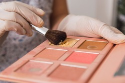 Makeup brush. A woman's hand holds a brush and a palette of eyeshadows.