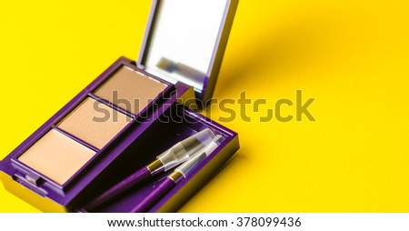 makeup brush and cosmetic powder close. Top view on a yellow background #378099436