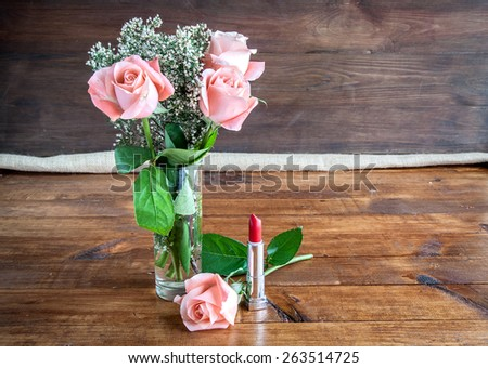 makeup brush and cosmetics on white wooden table
