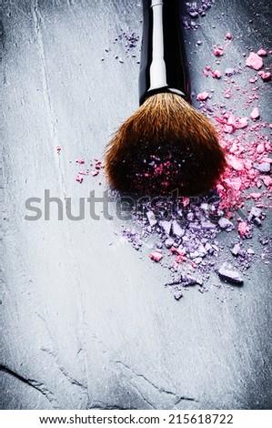 Makeup brush and crushed eyeshadows on dark background