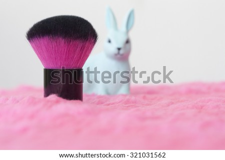 Makeup brush and rabbit plastic toy on pink fluffy cloth. Blur image, selective focus on the brush. Perfect as background for girls and makeup artists. Empty space for copywriting.