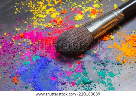 Makeup brush on a background with colorful powder. Makeup concept