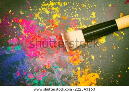 Makeup brush on a background with colorful powder. Top view