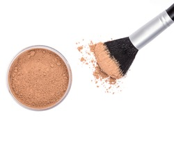 Makeup brush with open jar filled with loose cosmetic powder from above on white background