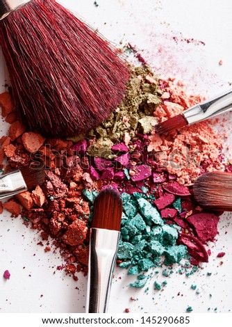 makeup brushes and multicolored eyeshadow on white - stock photo