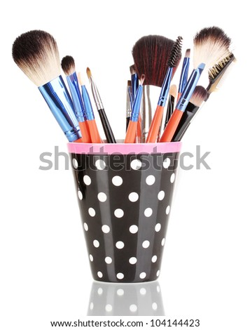Makeup brushes in a black polka-dot cup isolated on white