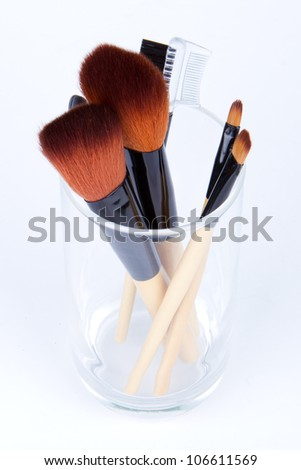 Makeup brushes in a glass of water