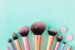 Makeup brushes on aqua colored background. Top view, flat lay, copy space