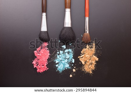 Makeup brushes on background with colorful powder. Crushed eyeshadow on black background. Abstract  background