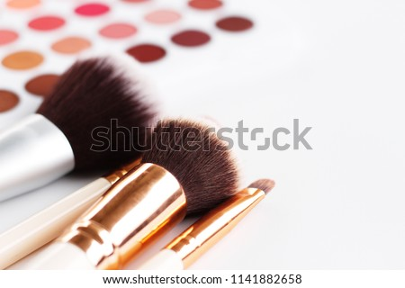 Photo of Makeup brushes placed diagonally on a white background leaving a blurred set of eye shadow palette behind. The image gives free space on the right of frame.