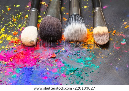 Makeup concept. Makeup brushes on a background with colorful powder