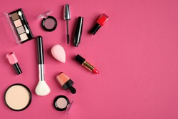 Makeup cosmetic products on pink background. Top view, flat lay.
