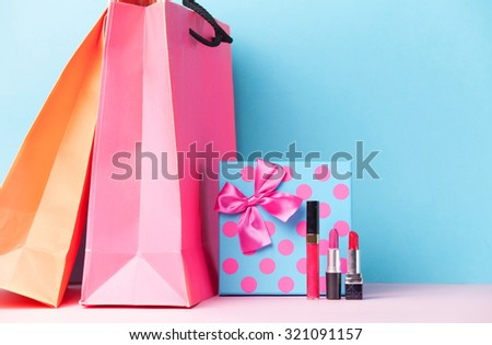 makeup cosmetics and gift box with shopping bags on blue background