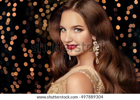 Makeup. Elegant hairstyle. Beautiful brunette smiling with long wavy hair, red lips makeup and fashion jewelry earrings. Attractive girl isolated on holiday party lights background.