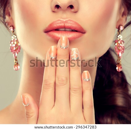 Makeup for eyes and lips ,eyeliner and coral lipstick. Beige trend manicured nails with rhinestones .