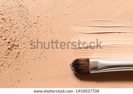 Makeup foundation background with beige liquid foundation texture, skin tone concealer smudges, nude face powder and cosmetic makeup brush