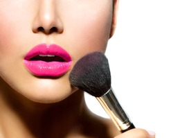Makeup. Make-up Applying closeup. Cosmetic Powder Brush for Make up. Perfect Skin. Purple Lipstick. Isolated on a White Background. Makeover