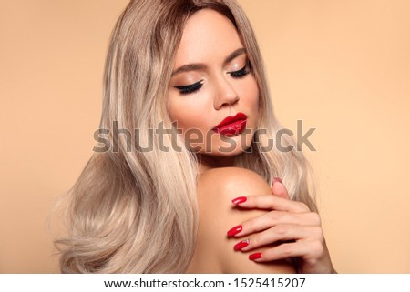Makeup, manicured nails. Beauty portrait of blonde woman with red lips, long healthy shiny blond hair style. Sensual girl with bright makeup isolated on beige backhround.