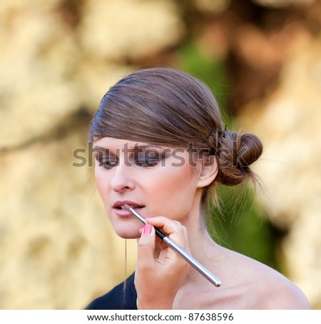 Makeup master applying lipstick with brush on caucasian girl lips