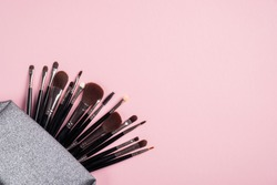 Makeup pouch with different black make up brushes on pink background. Flat lay, top view. Makeup shop banner design.