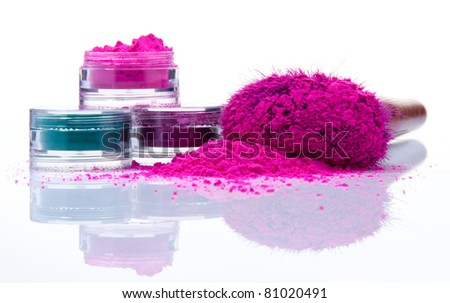 Makeup powder of different colors and brush