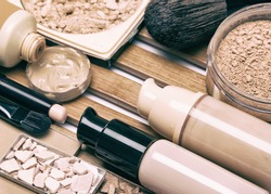 Makeup products for perfect complexion. Concealer, foundation and correcting, bronzing, highlighting powders with make up brushes. Toned image