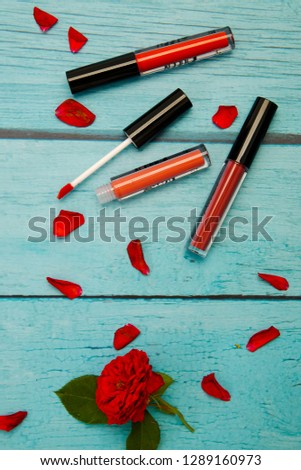 Makeup products new lipstick matte on blue wooden background, Valentine's Day and Mother's Day. Copy space. Flat lay , Photography minimal