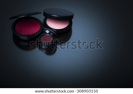 Makeup products on dark background with reflection. Copy space for your text. Studio shot. Horizontal picture