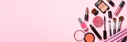 Makeup professional cosmetics on pink background. Long banner format.