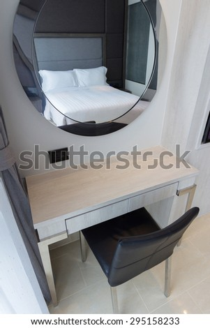 makeup table and oval mirror in bedroom.