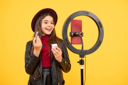 makeup tutorial. influencer. happy teen girl use selfie led. kid beauty blogger. cheerful child do makeup. vlogger with powder brush. making video blog on phone. blogging ring lamp. weblog and vlog.