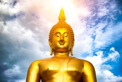 Makha Bucha Day, Visakha Bucha, a large shadow Buddha statue behind a golden sunset in Thailand