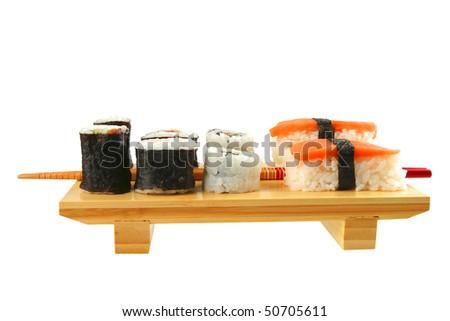 maki and sashimi sushi on wooden plate with sticks - stock photo