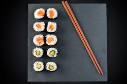 Maki Rolls Salmon Avocado on black plate and sticks top view