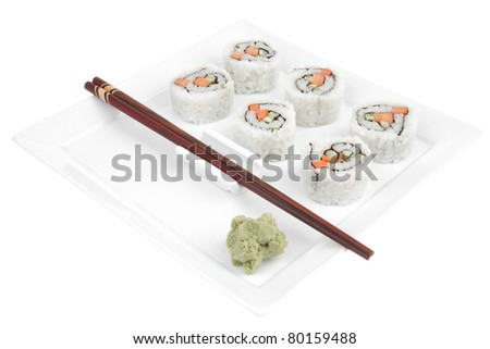 Maki Sushi - California Maki Roll made of fresh raw Salmon, Cream Cheese and Avocado inside. Served with wasabi . Isolated over white background on square plate