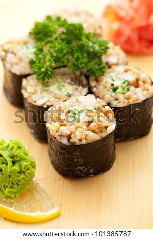 Maki Sushi - Roll with Brown Rice and Green Lettuce inside. Garnished with Ginger and Wasabi