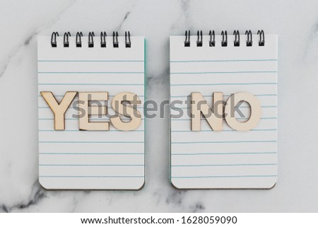 making a choice and facing doubts conceptual still-life, notepads with opposite Yes and No choices