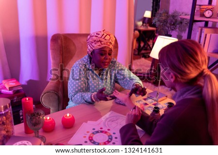 Making a prediction. African american plump fortune-teller wearing a huge ring making a prediction
