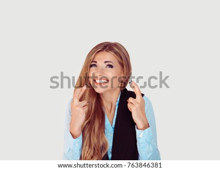 Making a wish. Closeup portrait of a young woman crossing fingers wishing and praying for miracle, hoping for the best, isolated on white background. Positive emotion facial expression feelings #763846381