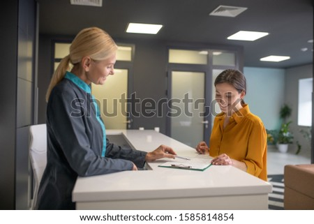 Making an appointment. Blond woman in grey jacket talking to female visitior