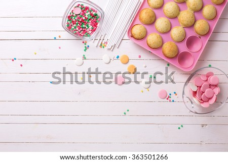 Making cake pops on white wooden background. Selective focus.Place for text.