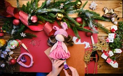 Making Christmas gift doll for kids. Closeup view of a handcrafted doll with accessories . High quality photo
