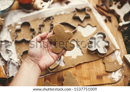 Making christmas gingerbread cookies. Hand holding raw gingerbread man cookie on background of dough, metal cutters and anise, ginger, cinnamon, pine cones, fir branches on rustic table. #1537751009