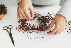 Making christmas wreath on white wooden table at home, holiday advent. Female hands making simple christmas wreath with red berries on white wooden table with thread and scissors