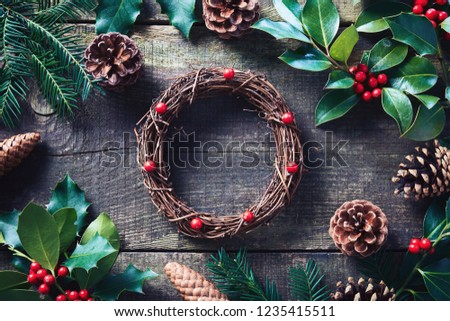 Making Christmas wreath using fresh and all natural materials. Christmas wreath with red berries and cones on wooden table.