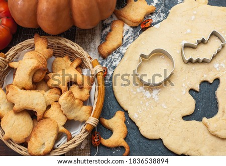 Making cookies for Halloween. Cut out cookies from dough in the form of pumpkin, cat, ghost and bat. stock photo