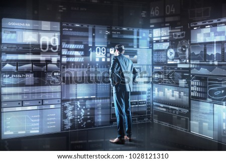 Making decision. Calm concentrated young programmer with virtual reality glasses standing in front of a giant transparent screen and thoughtfully looking at it while making important decision #1028121310