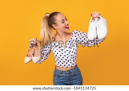 Making Decision. Portrait of smiling lady holding pair of high heels shoes and white sneakers in hands, can't choose between footwear and style, isolated over orange studio background Foto stock ©